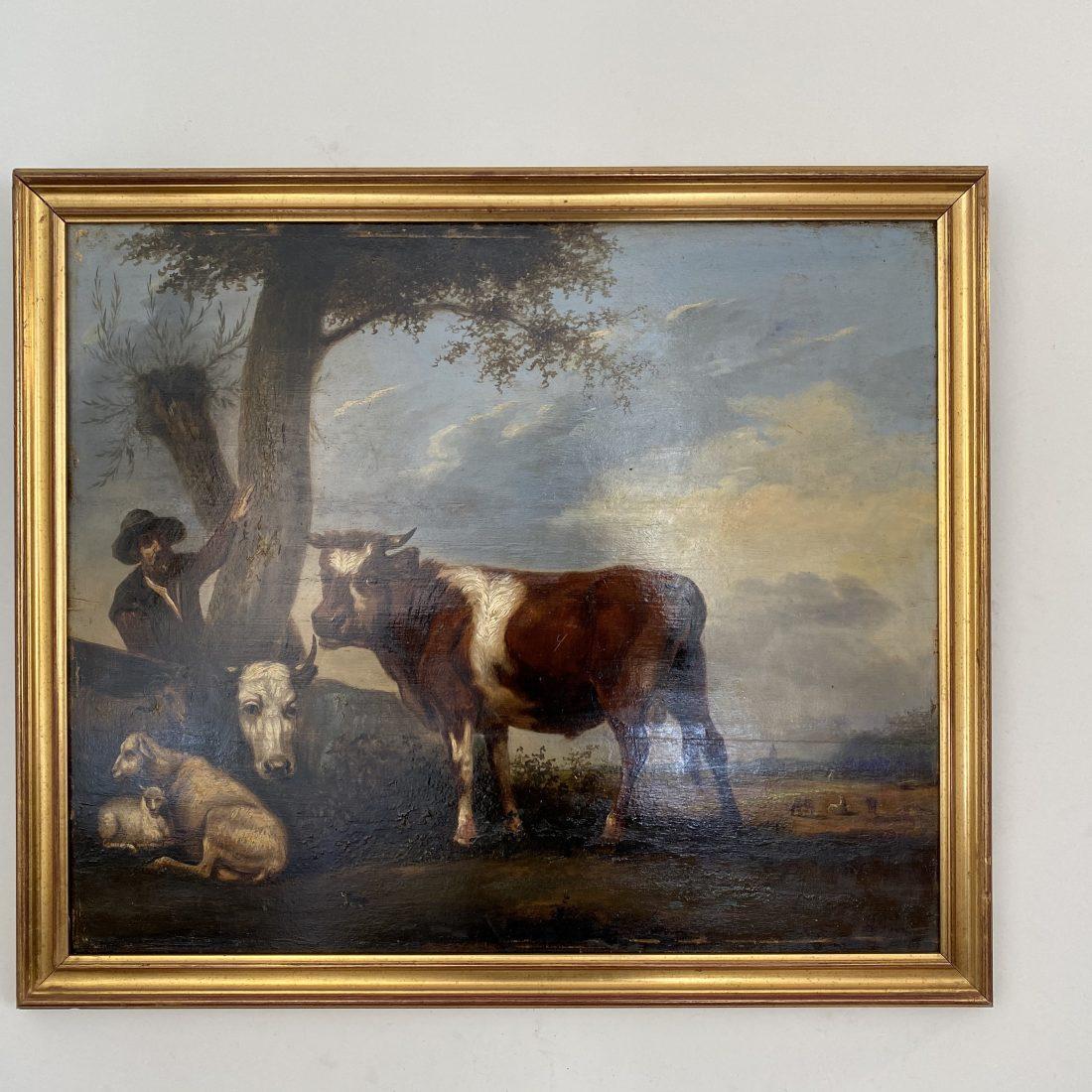 Een boer met zijn koeien en schapen in een bosrijke omgeving