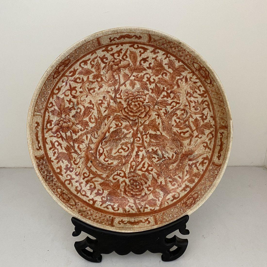 Een gecracqueleerd porseleinen schotel met ijzerrood decor van diverse bloemen & twee draken (iron red), Kangxi gemerkt